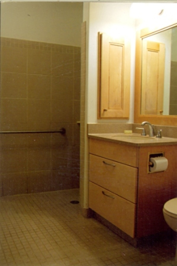 This bathroom has a curbless shower suitable for wheelchairs and ample storage in the drawers beneath the sink.